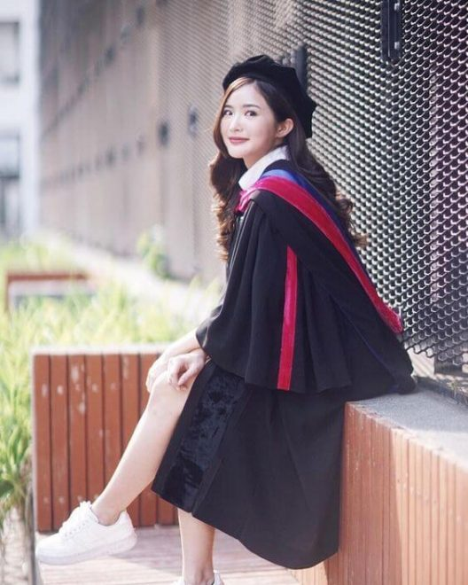 conserve- girl sitting wearing a black graduation gown and cap