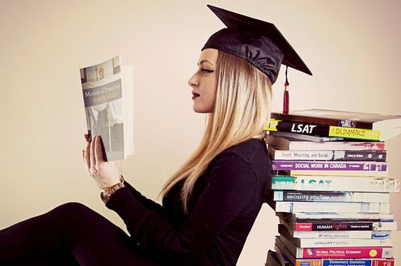 DEBTCOM Inc - girl reading wearing a graduation cap and leaning on a pile of books
